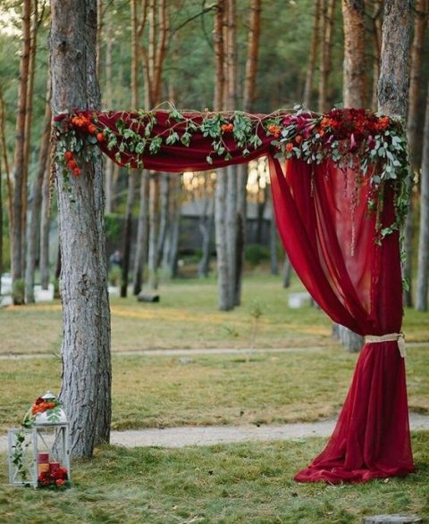 two living trees are used to create a wedding arch dressed up with burgundy fabric, greenery and bold blooms