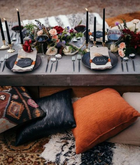 a Halloween picnic table setting with black candles, lush florals, antlers and matte black chargers