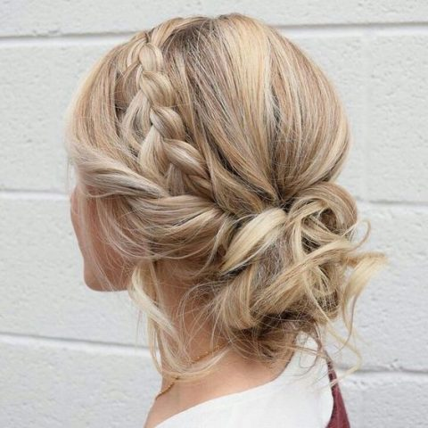 a boho messy wavy low bun with a large side braid plus a twisted braid and some locks down
