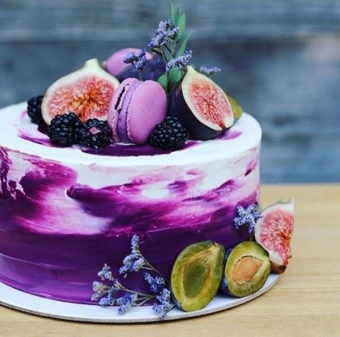 a bold brushstroke purple buttercream wedding cake topped with figs, blackberries and lavender