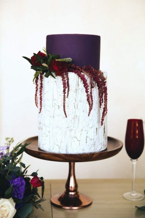 a bold wedding cake with a purple tier and a buttercream neutral one plus blooms