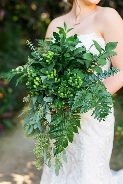 a cascading wedding bouquet with leather leaf fern, seeded eucalyptus, baby blue eucalyptus, foliage and hypericum berries