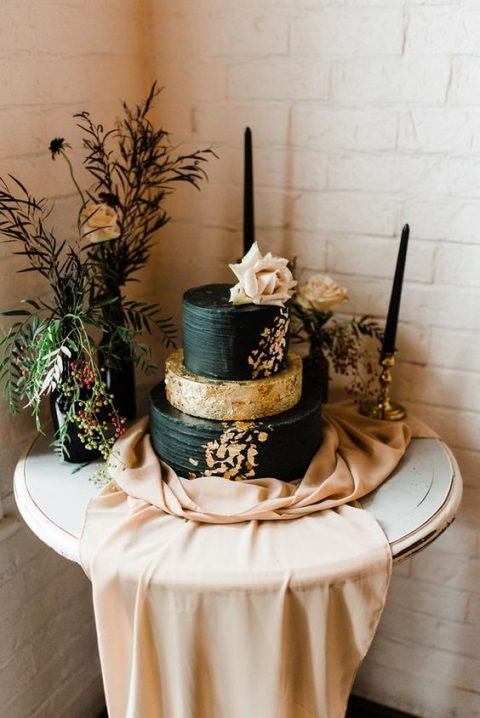 a chic black and gold foil cake topped with a large blush rose