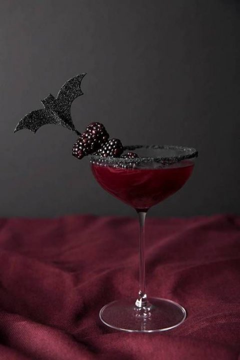 a chic idea of serving your cocktails with a black glitter rim glass, berries on a stick and a bat