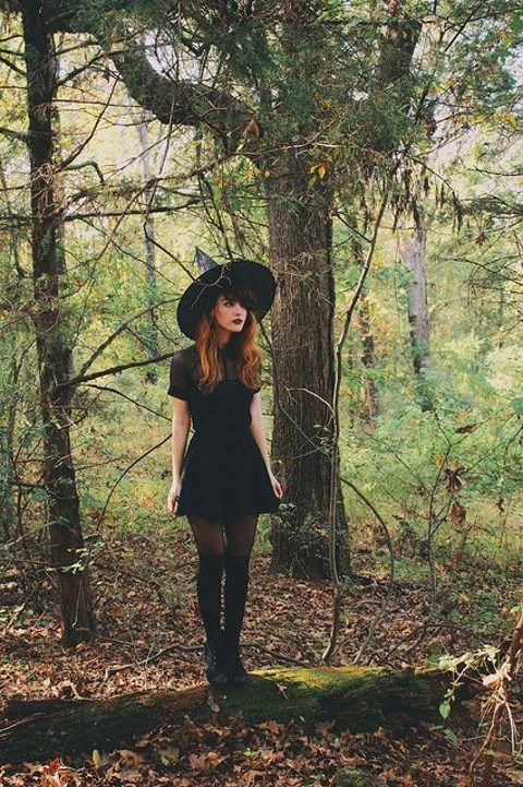 a chic modern witch outfit with a blakc mini dress, tall boots and a witch hat