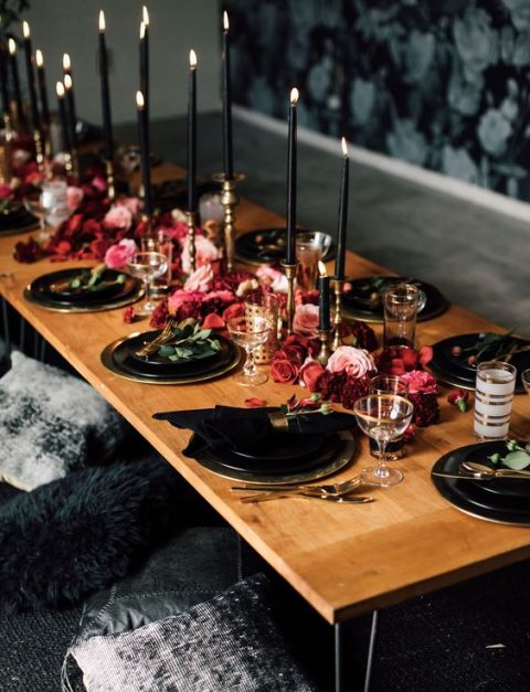 a chic red and black bridal shower table setting with black candles and gilded touches