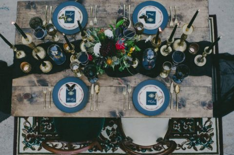 a chic tablescape with a black runner and candles, blue chargers, moody blooms and gilded touches