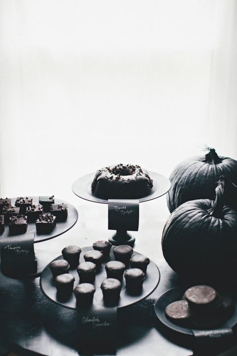 a dessert table done in all-black with black pumpkins and silver calligraphy