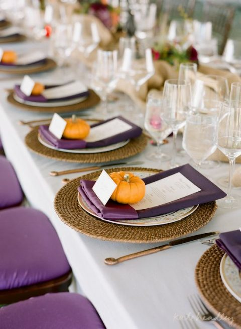 a fall table setting with purple napkins, menus and chairs