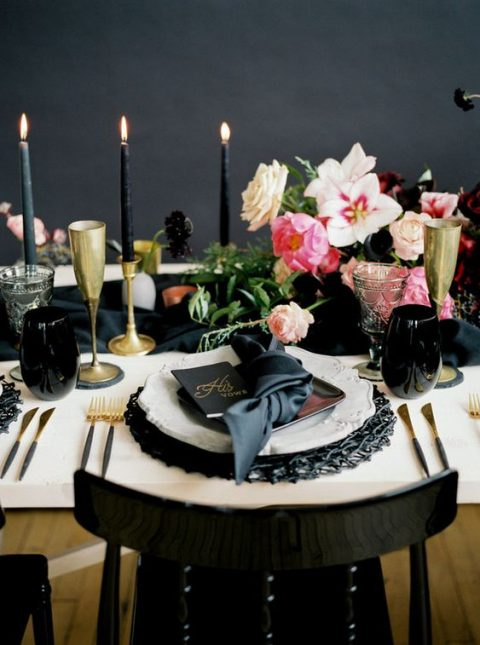 a gorgeous moody table setting with black and gold touches, bright blooms and black candles