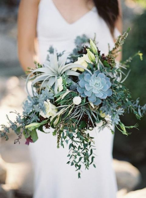 a greenery cascading wedding bouquet with succulents, air plants and herbs and foliage