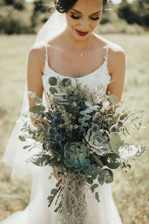a greenery wedding bouquet with eucalyptus, blue thistles and succulents looks very romantic