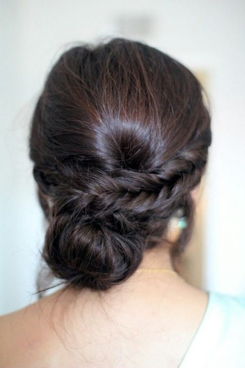 a low bun with a single side braid and a bump for a whimsy take on a usual low bun