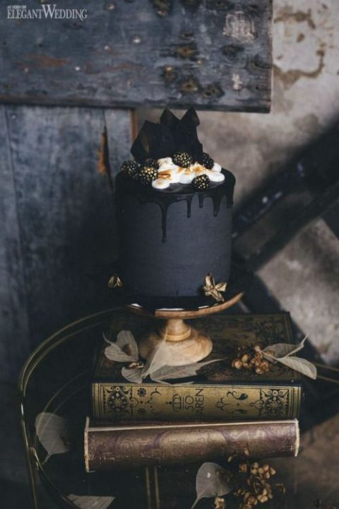a matte black cake with black drip, cream, dark chocolate shards and gilded blackberries