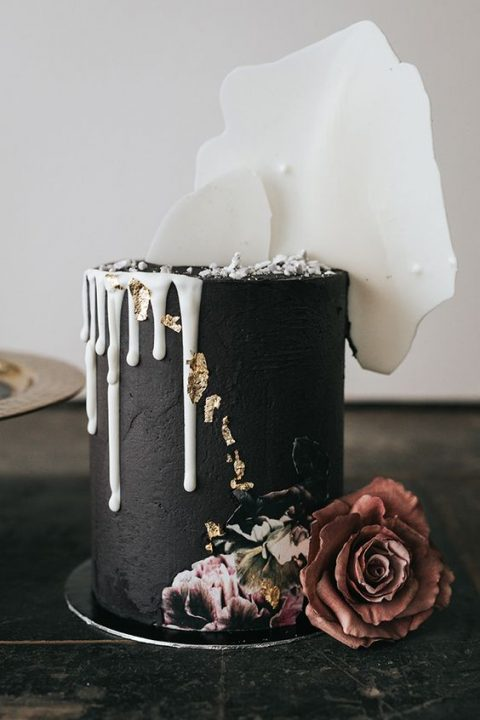 a matte black cake with white chocolate shards and drip and handpainting