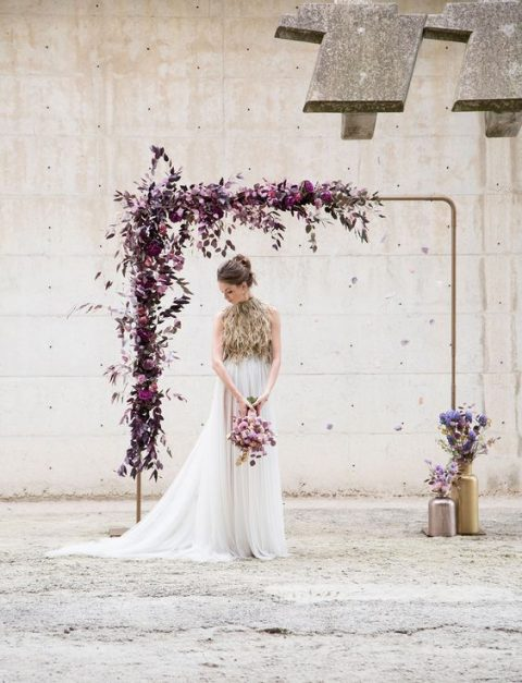 a modern wedding arch done with all shades of purple blooms and dark foliage and metallic vases