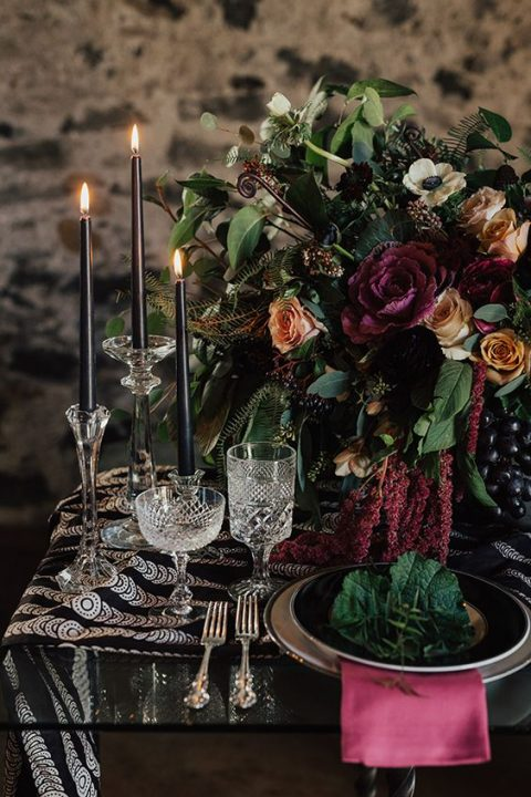 a moody tablescape with a printed runner, black candles, pink textiles and a textural centerpiece