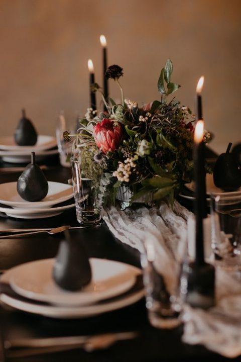 a moody tablescape with a textural floral centerpiece and black pears and candles