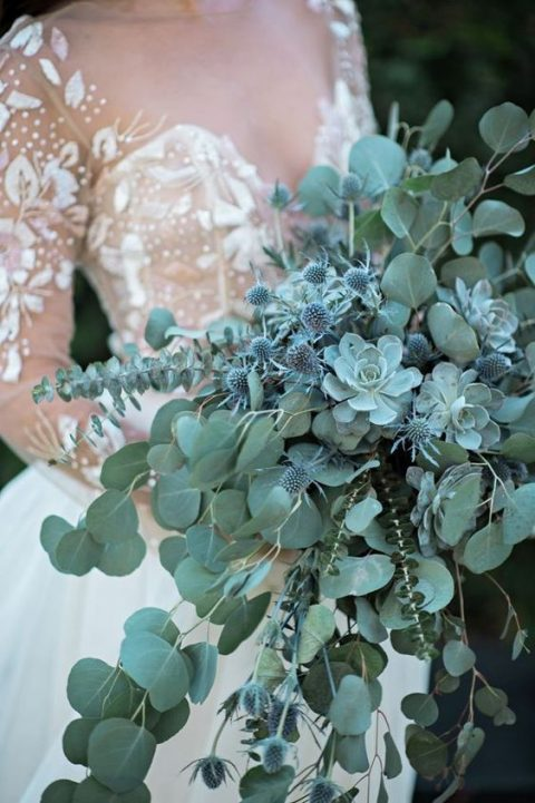 a pale green cascading wedding bouquet with eucalyptus, succulents and blue thistles