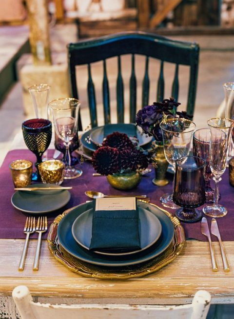 a purple table runner and matching glasses plus black and gold touches