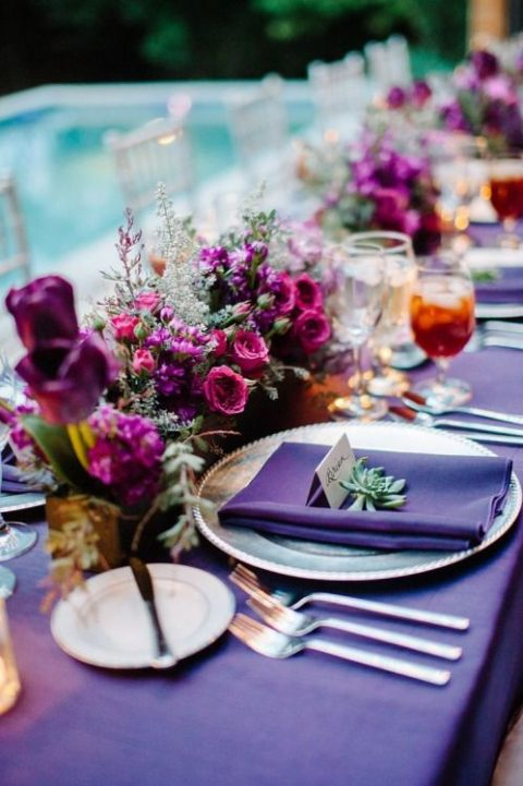 a purple table setting with jewel-tone blooms and succulents