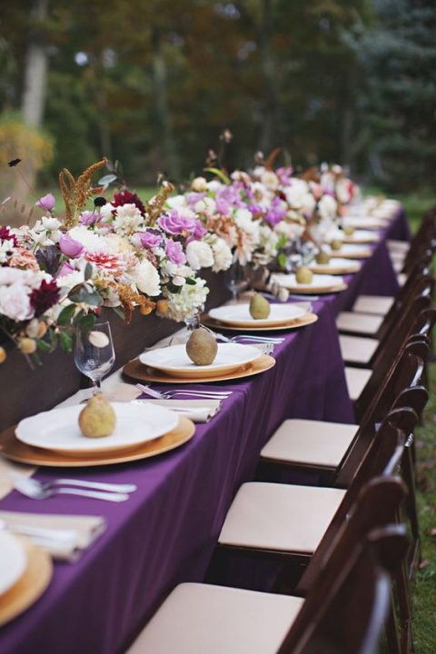 a purple tablecloth plus a table centerpiece with lush blooms and herbs