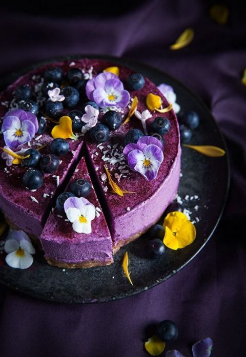 a purple wedding cheesecake with edible flowers and blueberries