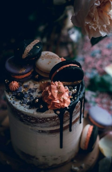 a semi naked cake with chocolate drip, colorful macarons and creamy blooms