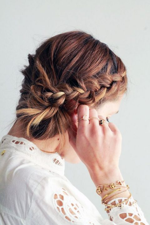 a side braided messy low bun hairstyle for a boho cihc bride