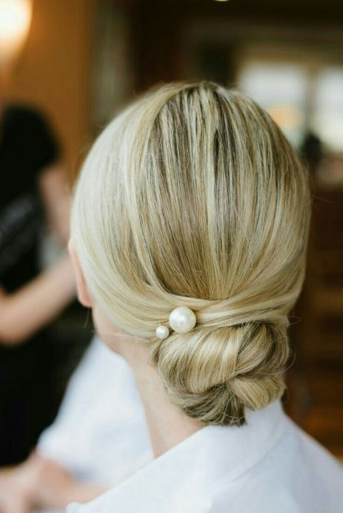 a sleek twisted low bun accented with large pearl pins for a minimalist bride