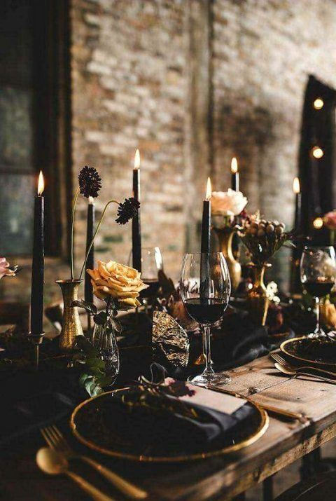 a super dark wedding tablescape with black candles, textiles and elegant gilded touches
