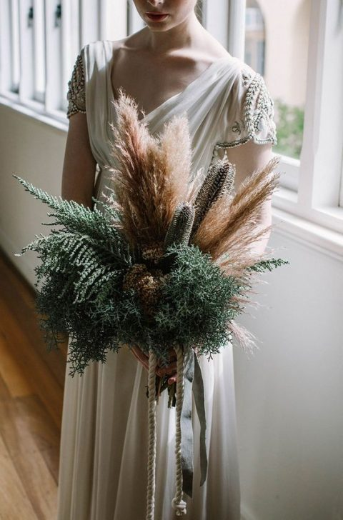 a textural greenery, dried blooms and pampas grass wedding bouquet for a boho bride
