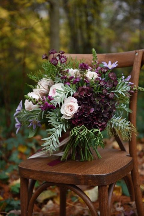 a textural wedding bouquet with much greenery, lavender, deep purple blooms and blush roses