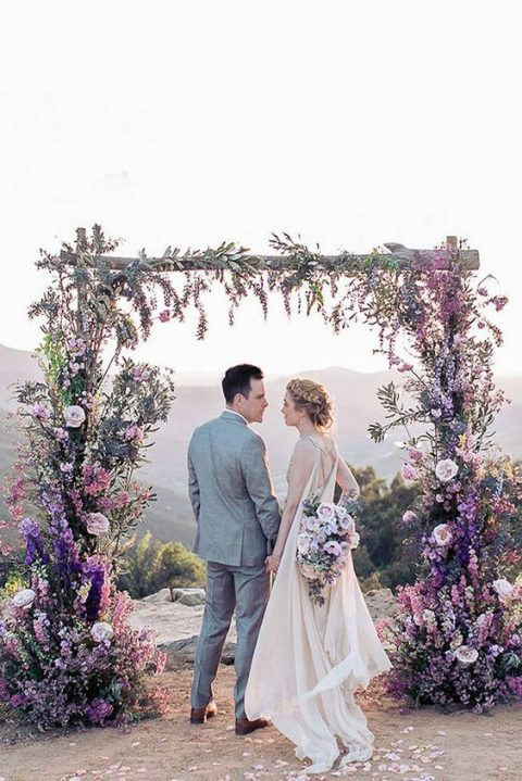 a wedding arch decorated with lush purple, blush, pink and white blooms and greenery