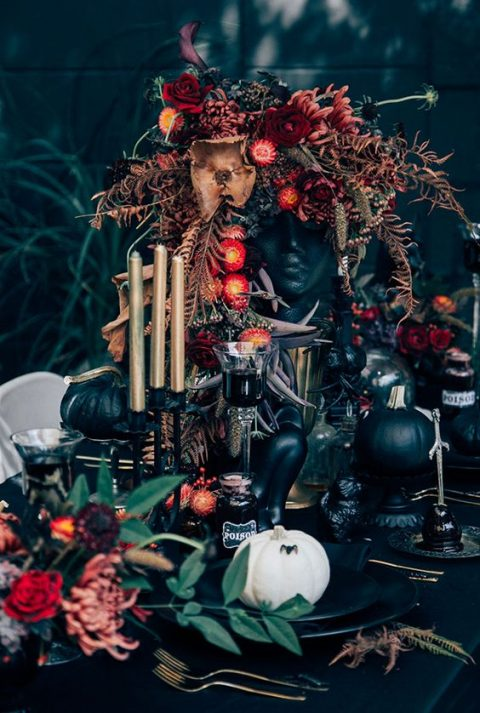 a wedding centerpiece of a human head and decadent florals, gilded candles and black pumpkins