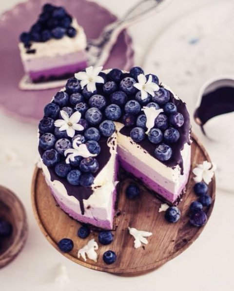 an ombre purple wedding cake with chocolate drip and blueberries on top