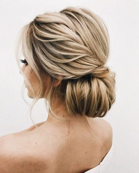 an oversized low bun with a twisted side braid and some waves down for a refined feel