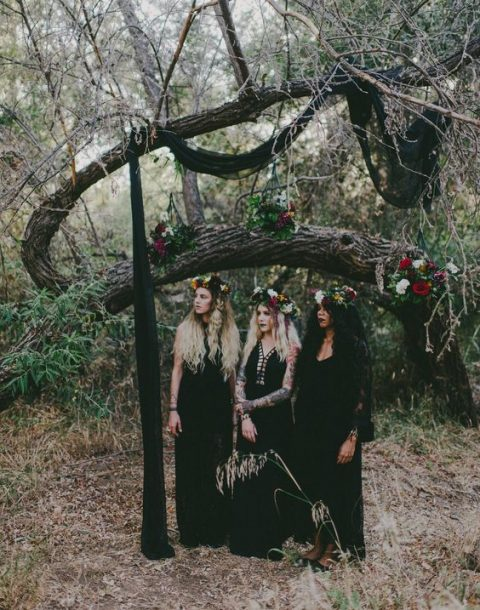 bridesmaids-to-be dressed in mismatching black gowns and wearing floral crowns