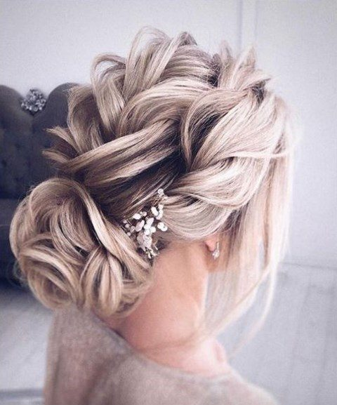 loose braids on top, a low twisted bun and a little rhinestone hairpiece for a chic bridal look