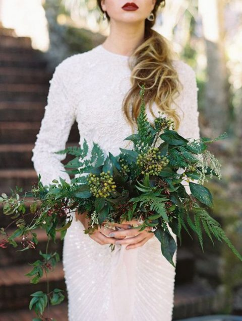 very textural and a bit cascading wedding bouquet of greenery and some berries