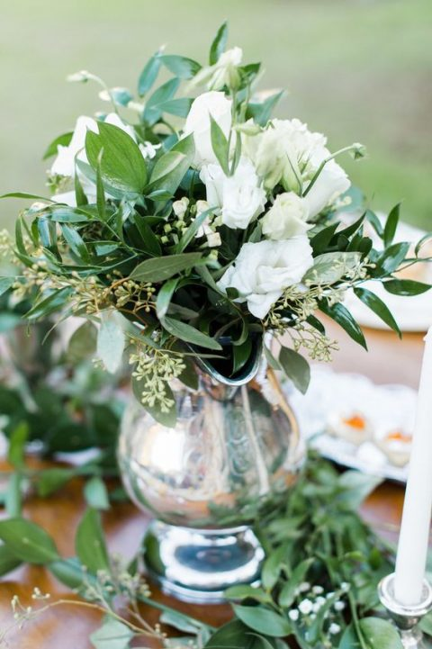 a beautiful winter wedding centerpiece of a silver pitcher and white blooms and greenery
