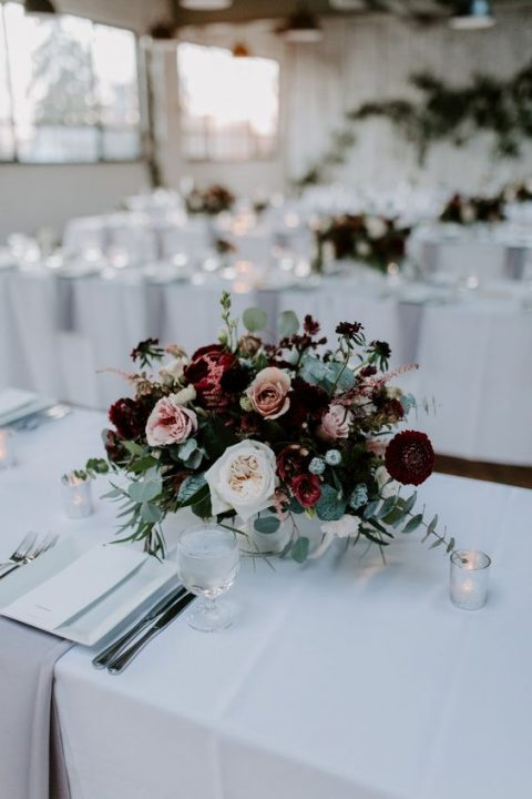 a bright winter floral centerpiece with burgundy, blush and white blooms and pale greenery