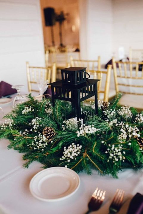 a candle lantern surrounded with evergreens, pinecones and baby_s breath