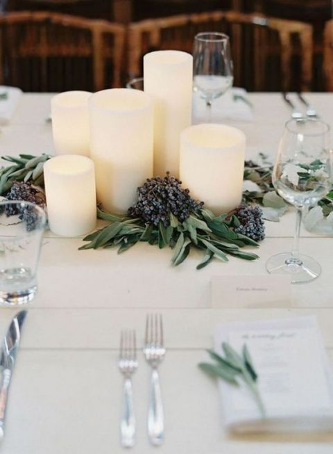 a chic and simple centerpiece of pillar candles placed on the table with privet berries