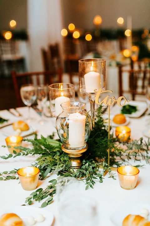 a chic centerpiece with candles in gold candle holders, fresh greenery and a calligraphy table number