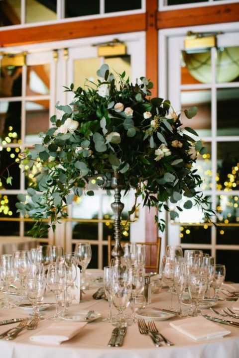 a chic tall floral centerpiece of lush greenery and blush blooms