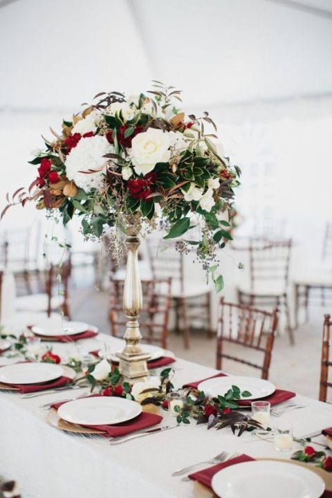 a chic tall wedding centerpiece with burgundy and white blooms and gold and green foliage
