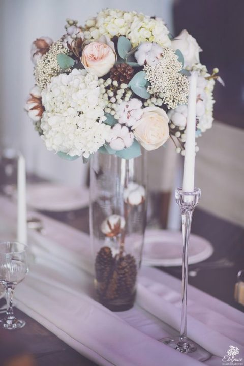 a chic winter wedding centerpiece of white and blush blooms, berries, cotton and pinecones