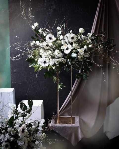 a frozen artful centerpiece of white anemones, willow and greenery