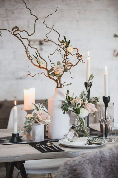 a frozen-like centerpiece with white vases, branches, candles and blush roses